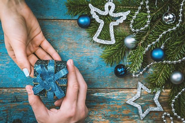 男の手はギフトボックスを与え、女性の手はクリスマスの装飾が施された背景の上面図を引き継ぐ