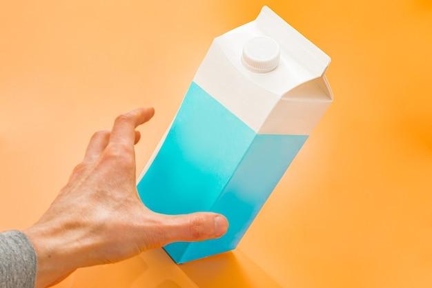 Ман рука хватает сине-белый бумажный пакет с молоком на оранжевом фоне. большая емкость.