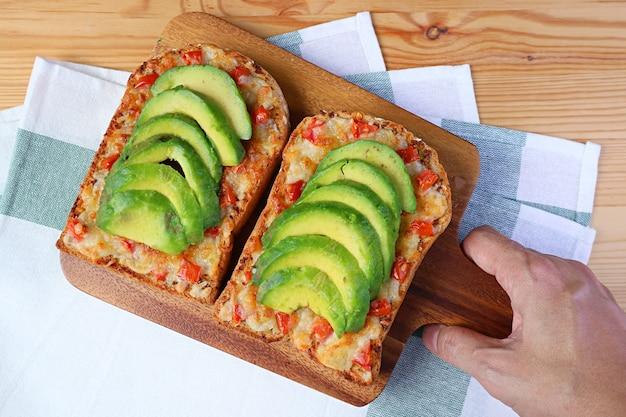 Ман рука держит макет жареного сырного тоста с помидорами и нарезанным авокадо