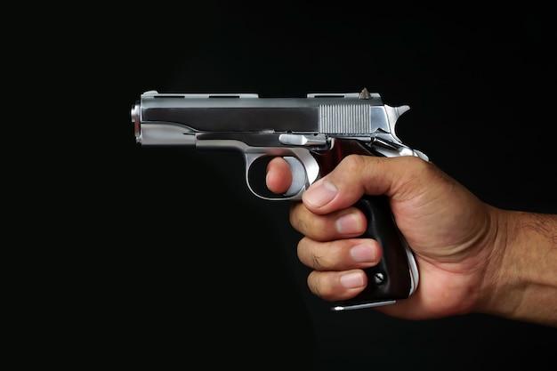 검은 배경에 총을 들고 손을 망