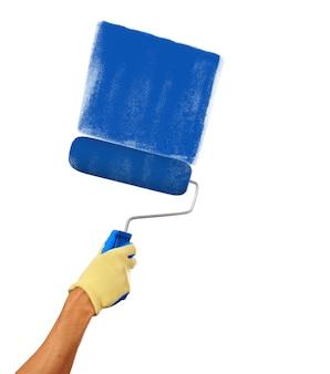 白い背景で隔離の青いペンキで描画するペイントローラーを持っている男の手