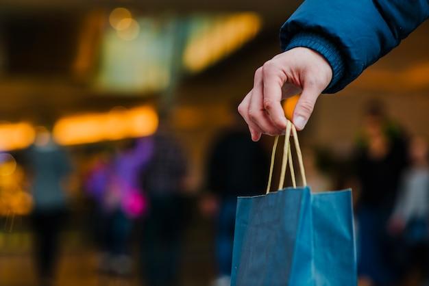 Mans hand holding shopping bag