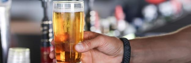 男の手はバーでビールのガラスを保持します