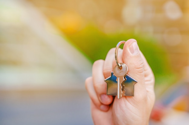 A mans hand holds the keys to a new house against the background of highrise buildings