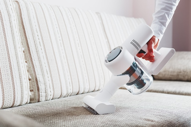 A mans hand holds a modern wireless vacuum cleaner for cleaning the sofa in the house