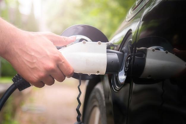 Ман рука вставляя вилку зарядного устройства в электромобиль на фоне зеленой среды. новый энергетический автомобиль, nev, загружается электричеством. экология, современные автомобили