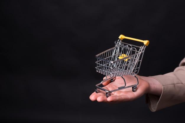 マンの手は黒い背景に小さなショッピングカートを持っています。