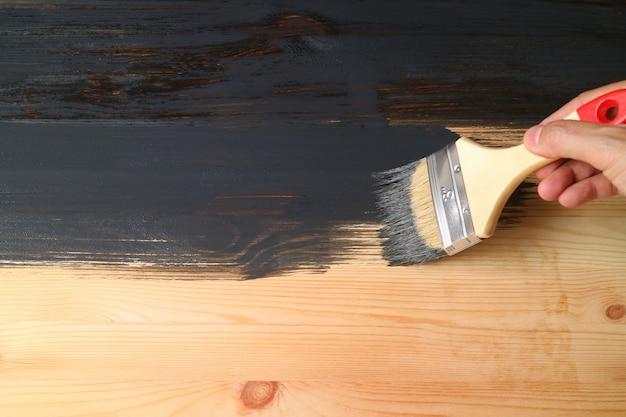 Ручная роспись поверхности доски из натурального дерева в черный цвет