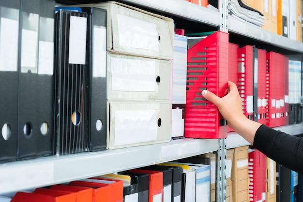 棚からファイルを含む空白のブラインドフォルダを手で選ぶ人。
