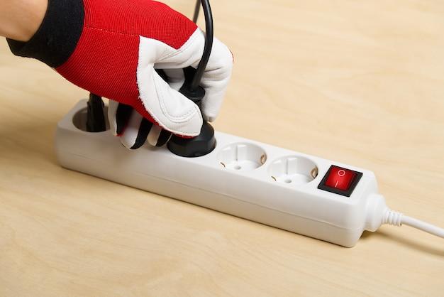연장 코드를 연결하는 손 망. 연장 코드를 서로 연결하는 전기의 근접 촬영.