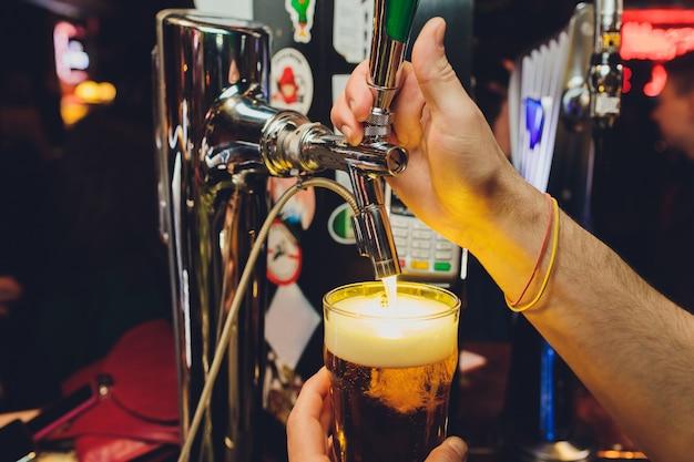 Ман рука наливает пинту пива за барной стойкой.