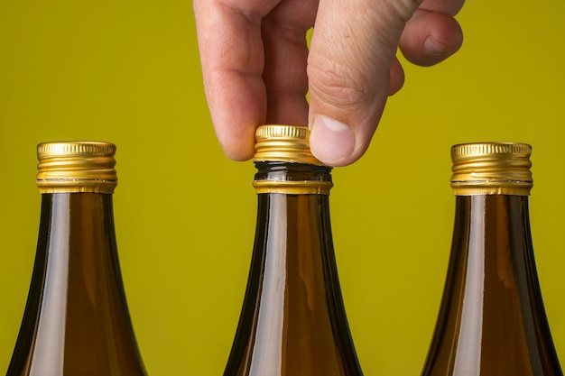 A mans hand removes the cap from a glass beer bottle