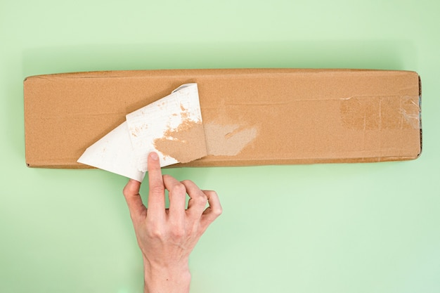 Mans hand ripping off a sticker from a long delivery parcel on a light green background.