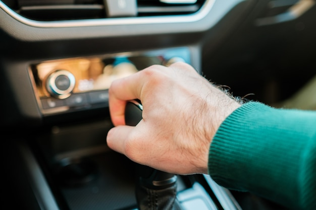 A mans hand shifting gearbox in the modern auto man shifting a stick of a manual or automatic
