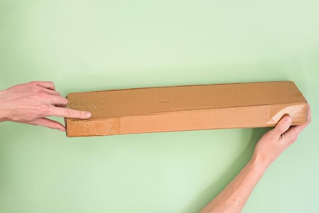 Mans hand shows by index finger on a smushed corner of long delivering paper parcel