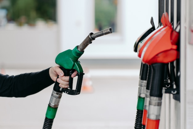 Mans hand using fuel nozzle at petrol station
