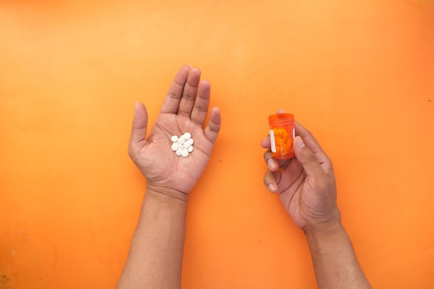 Mans hand with medicine spilled out of the pill container
