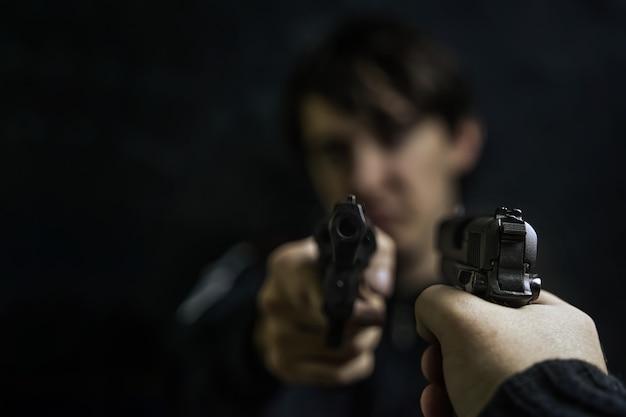 두 명의 도둑이나 살인자 총기의 리볼버 총격전으로 범인을 가리키는 권총을 든 남자의 손...