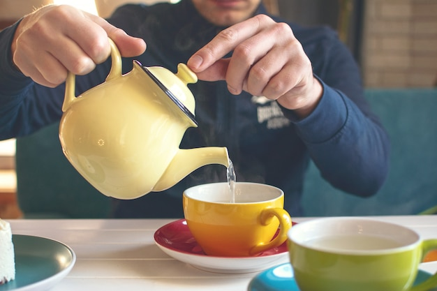 Mans hand with a yellow teapot