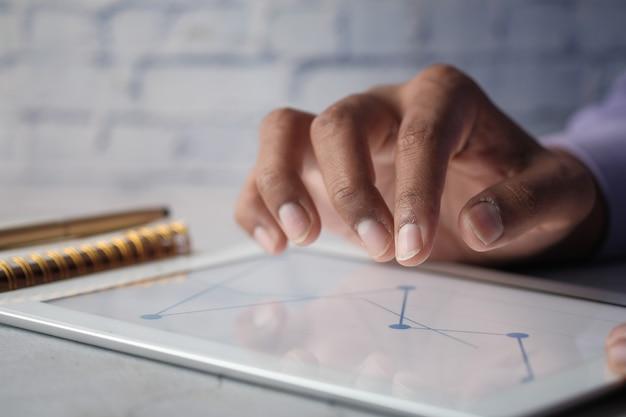 자체 생성 차트를 사용하여 사무실 책상에서 디지털 태블릿으로 작업하는 손