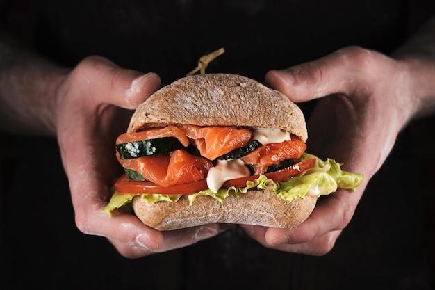 Мужские руки держат бутерброд с лососем, огурцами, помидорами и майонезным соусом