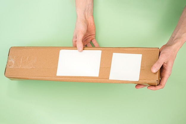 Mans hands holds a long paper parcel with white empty labels on a light green background