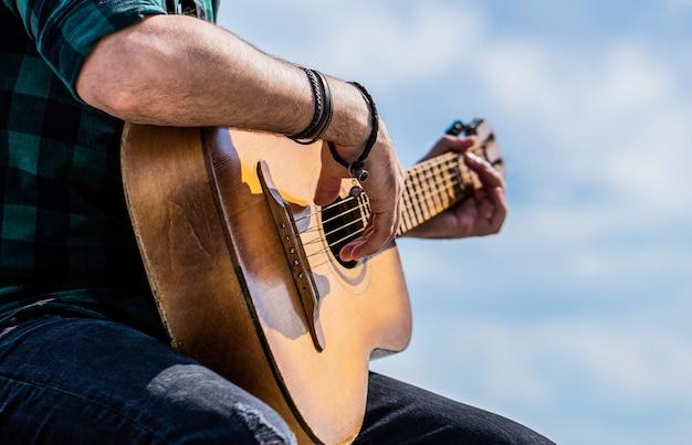 어쿠스틱 기타를 연주하는 손을 닫습니다. 어쿠스틱 기타 연주