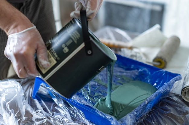 Mans hands in rubber gloves  pouring green paint from bucket into tray