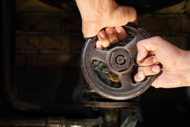 Руки человека пытаются повернуть ржавый вентиль на трубах котельной.