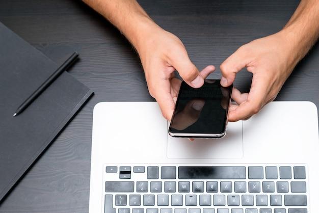 Ман руки печатать на смартфоне во время работы на портативном компьютере на старинном деревянном столе