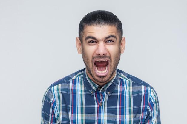 남자의 포효! 눈을 감고 비명을 지르는 화난 사업가. 실내, 스튜디오 촬영. 회색 배경
