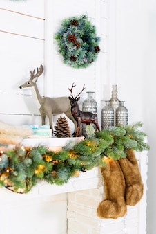 Mantelpiece with christmas decorations. cozy winter scene. white interior details with lights.