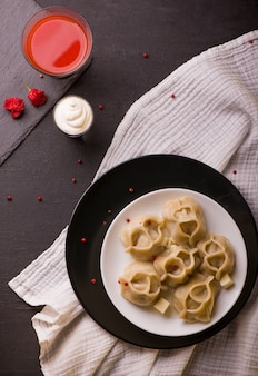 Manti or manty dumplings in a traditional bowl on wooden table.