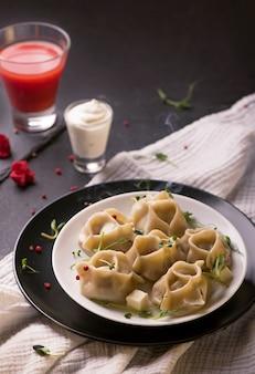 木製のテーブルの上の伝統的なボウルにマンティまたはマンティ餃子。テキストのバナーメニューレシピの場所。冷凍食品。食事の計画