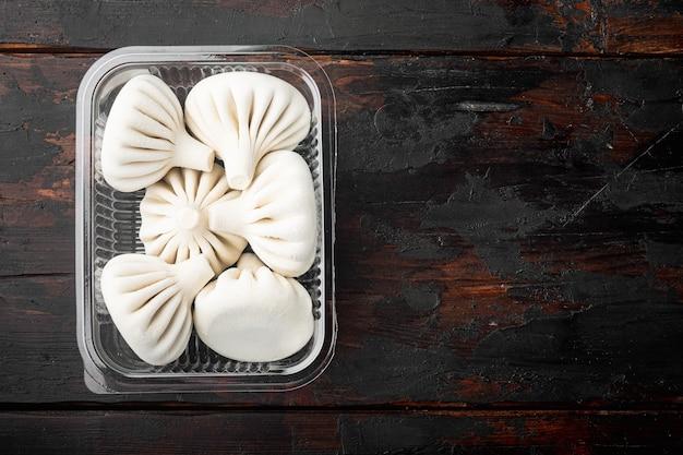 Манты или пельмени с манти, популярный азиатский набор блюд, в пластиковом подносе, на старом темном деревянном столе