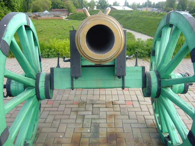 The mantle of an old cannon on wheels aimed at a frame standing on a stone pedestal