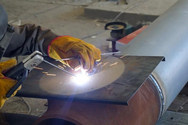 製油所の技術パイプラインと金属構造物の手動アーク溶接。