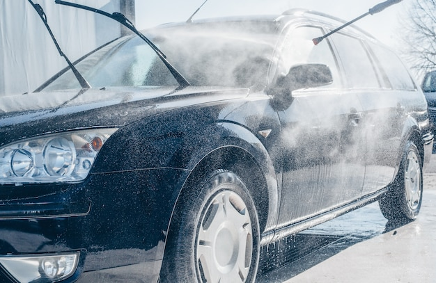 Manual car washing, cleaning using high pressure water in car wash, purifying concept