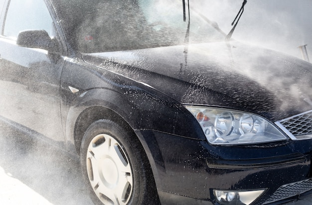Manual car washing, cleaning using high pressure water in the  car wash, purifying concept