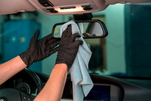 Manual cleaning of the rearview mirror in the car with the help of a rag