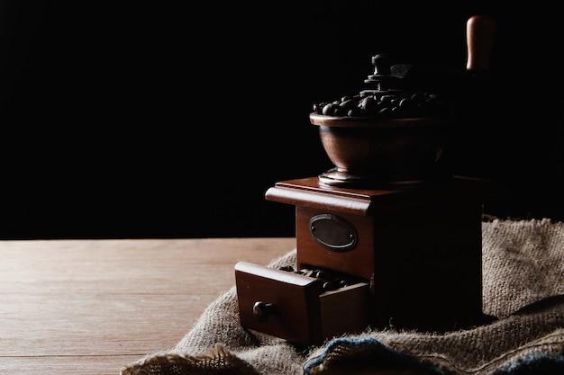 Ручная кофемолка на деревянном столе и мешковине на черном фоне