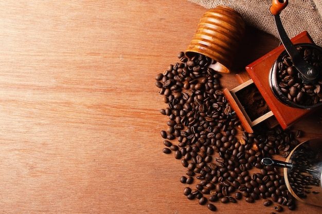 Manual coffee grinder teapot and wooden cup with spilled coffee beans on wooden table top view