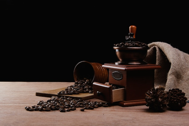 Manual coffee grinder and a wooden cup with spilled coffee beans on a wooden table