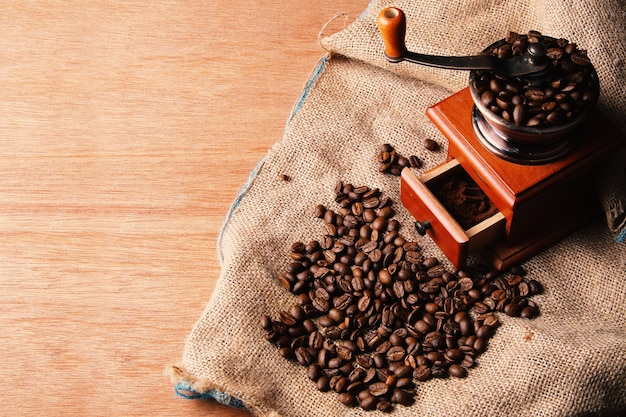 Manual coffee grinder on wooden table and burlap sack