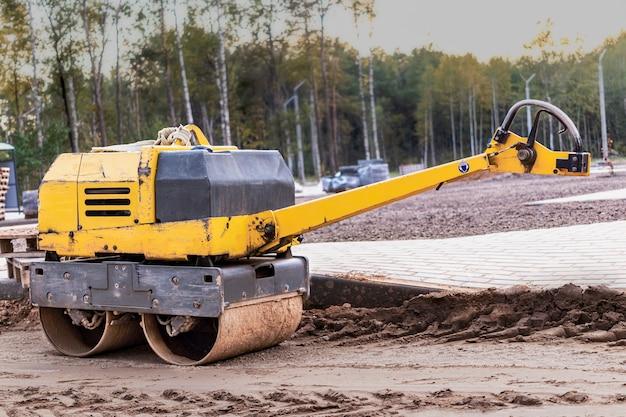Ручной компактный асфальтовый каток для утрамбовки грунта на стройплощадке. дорожные работы с использованием механизмов.