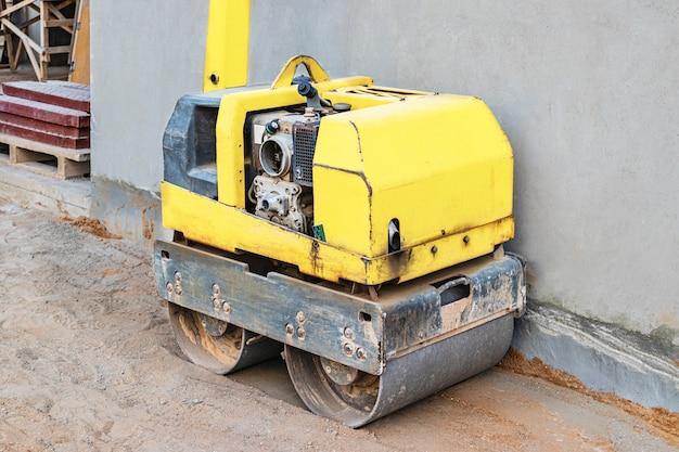 Ручной компактный асфальтовый каток для утрамбовки грунта на стройплощадке.