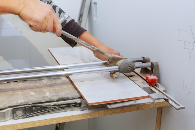 Manual cutting of ceramic tiles on a special machine for cutting tiles.