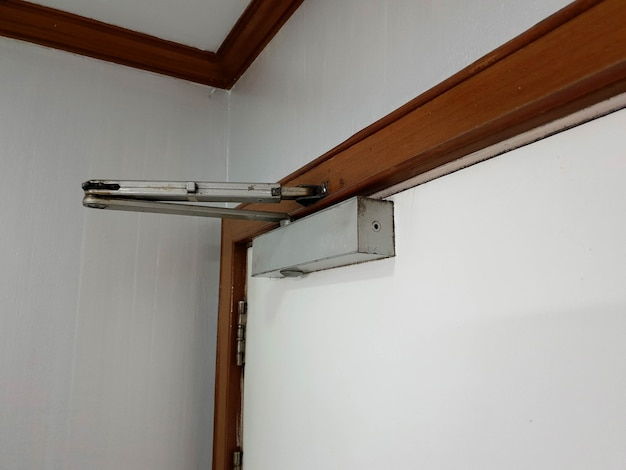 A manual door closer stores the energy used in the opening of the door in a compression