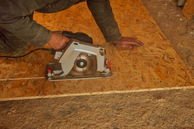 Ручная электрическая циркулярная пила вырезает деревянную пластину.