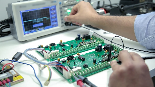Manual electronics soldering and oscilloscope testing
